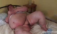 Kinky shorthaired BBW mature teasing her big assets in bed