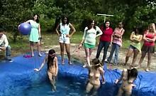 Girls wrestle in a homemade pool outside
